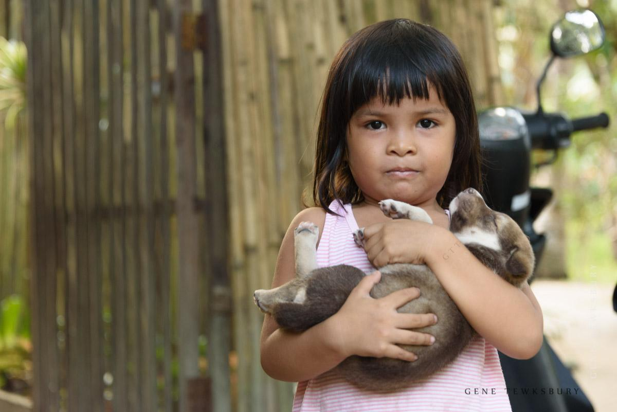 Filipina girl with dog in arms.